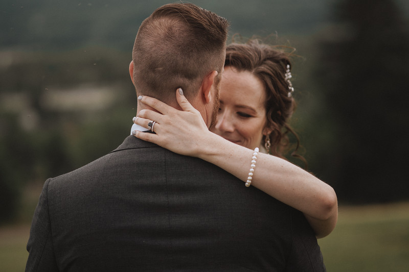 The bride holds the back of the grooms head as they embrace.