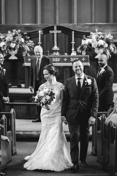 The bride and groom smiling as they walk back up the isle together.