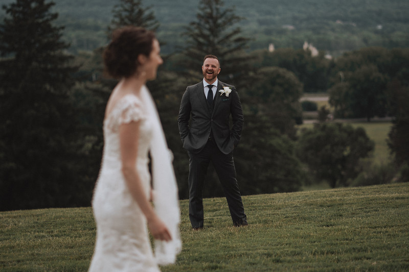 The bride turns towards the groom as he breaks and laughs.