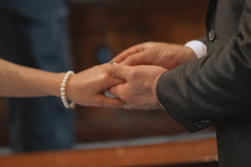 The groom gently holding the bride's graceful hand in one hand as he uses the other to slip the ring onto her finger.