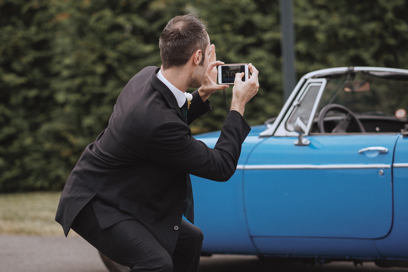 The Mike of Honor strikes a silly pose as he snaps a picture of the classic car with his phone.