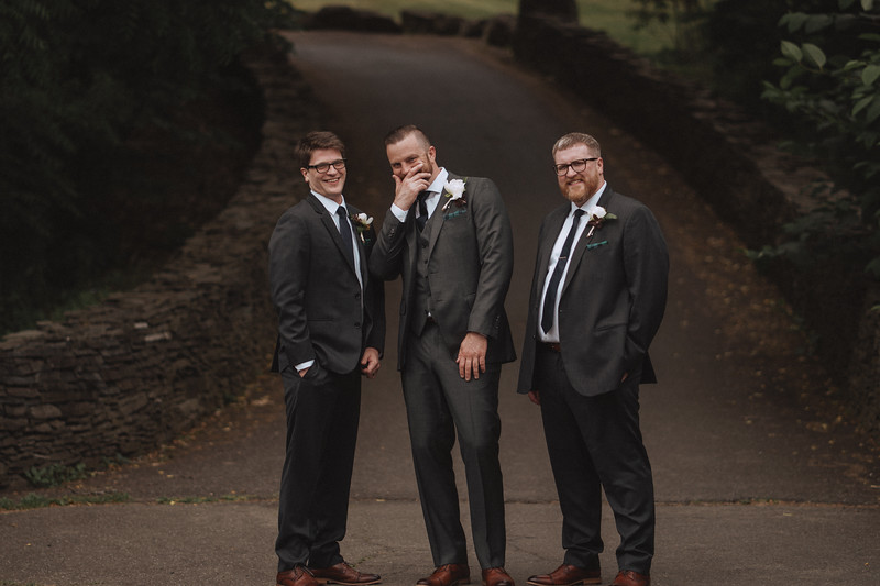 The groom standing between two of his groomsmen, laughing at the bottom of a stone walled pathway.