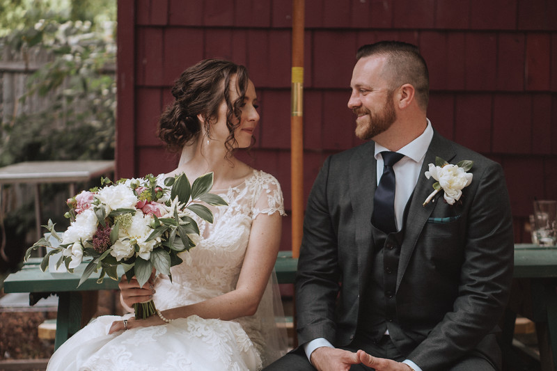 The bride and groom sitting on a picnic bench on the patio, smiling at each other as the bride holds her bouquet.