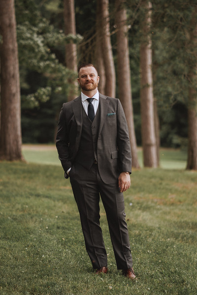 The groom standing with one hand in his pocket, looking serious and thoughtful, but happy.