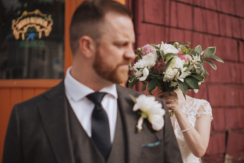 The bride hides her face with her bouquet behind the groom outside of the bar.