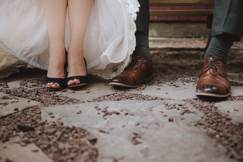 The bride and grooms shoes on the flat stone and gravel ground.