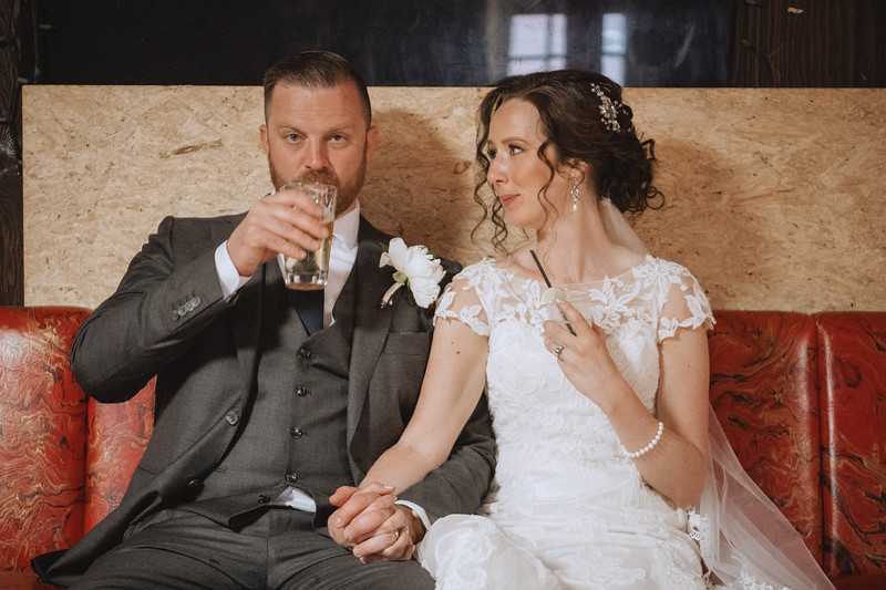 The groom finishes his beer and ironically looks serious as the bride smiles at him and they hold hands.