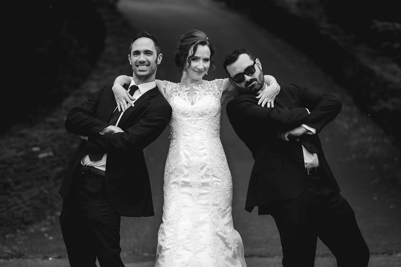 The bride smiling with her arms around her two Mikes as they make funny poses.