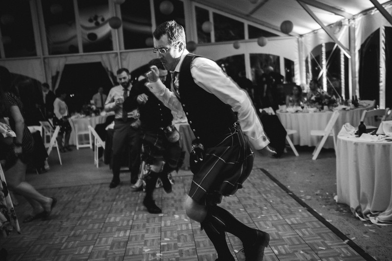 A Scottish man in a kilt dances to the pipers music.