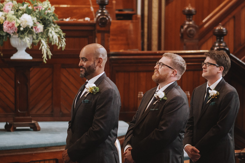 The groom's side of the wedding party smiling as they watch the ceremony.