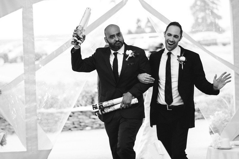 The Mike of Honor and a groomsman dance arm in arm into the reception holding confetti canon's.