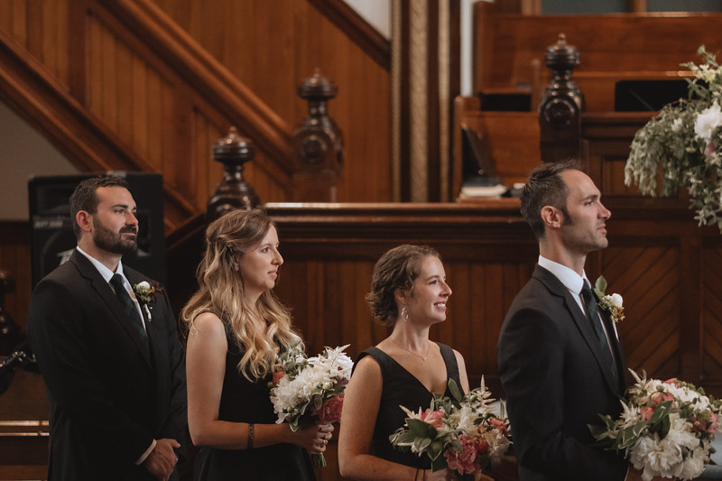 The bride's side of the wedding party smiling as they watch the ceremony.
