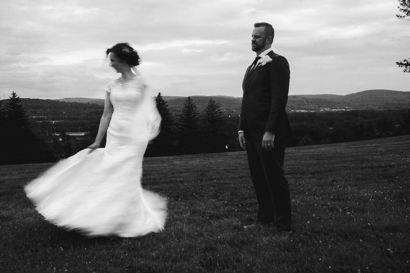 The groom watches as the bride twirls with a hilly valley and moody sky in the background.