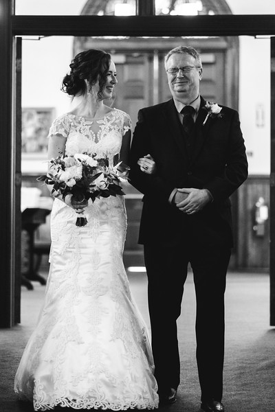 The bride standing in the church doorway, laughing at her father as he makes an anguished but funny face.