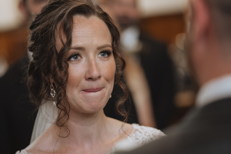 The bride biting her lip as she looks up at the groom.