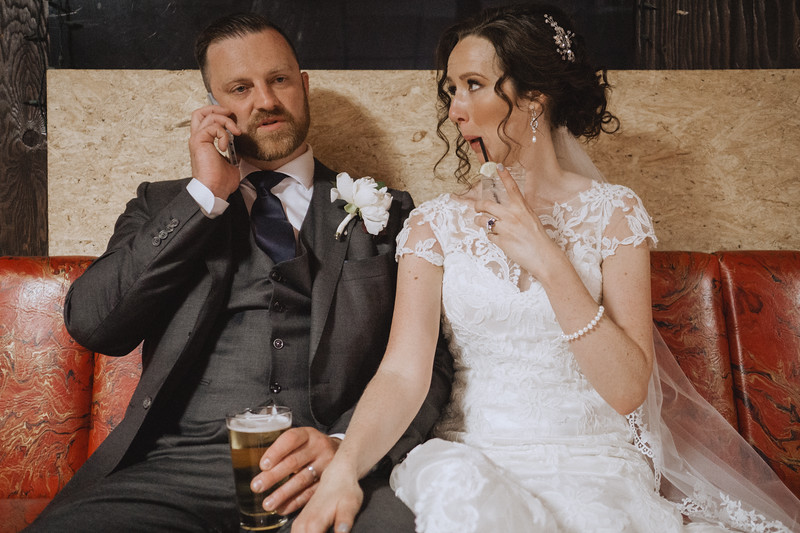 The groom talks on the phone while the bride makes a funny face at him while sipping her drink through a straw.