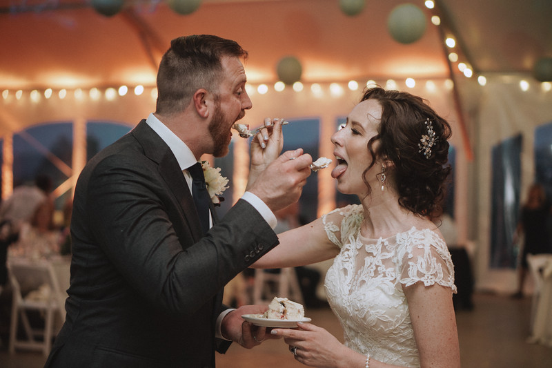 The bride and groom feed each other cake while making silly, exaggerated, eating faces.