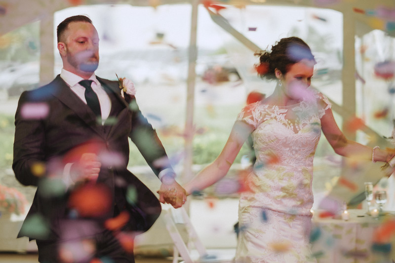 The bride and groom dance through confetti.