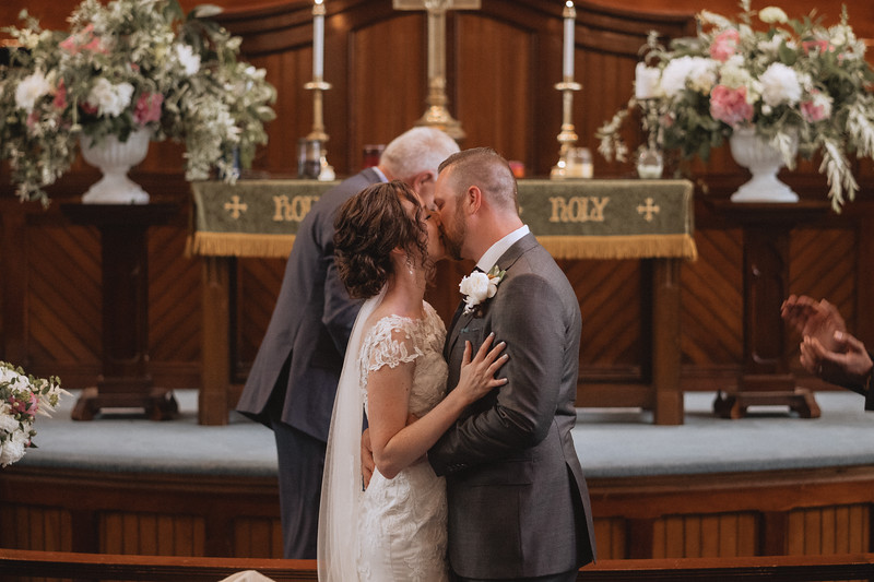 The bride and groom passionately kissing in front of the alter.