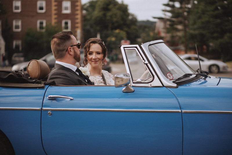 The bride smiles at the groom as they drive away in the convertible.