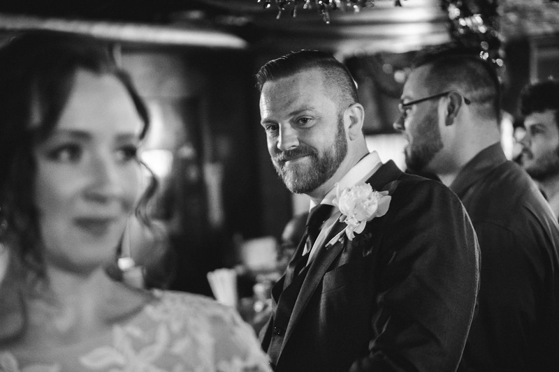 The groom smiles as he checks his bride out from while at the bar.