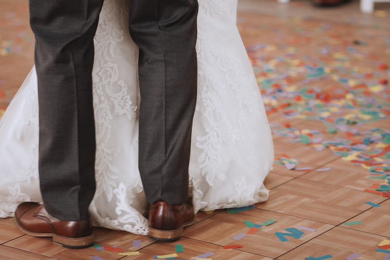 The bride and groom's feet as they dance through a confetti littered dance floor.