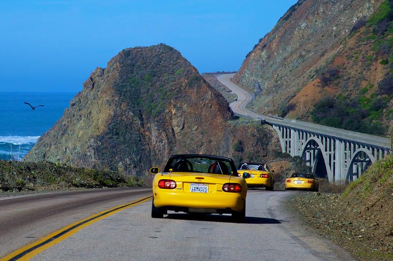 Three yellow Miatas approach Big Creek Bridge on Highway 1 in California.