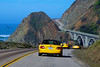 Three yellow Miatas approach Big Creek Bridge on Highway 1 in California.