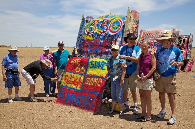 """Day 8: The """"artists"""" pose with their masterpiece.<br /> <br /> Things change fast at the Cadillac Ranch.  Greg and Mandie were running about 15 minutes behind us.  By the time they got to the scene of our crime, much of our masterpiece was already painted over."""