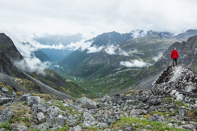 Man in red jacket standing on boulder overlooking glacially carved valley in THe Talkeetna Range, Alaska
