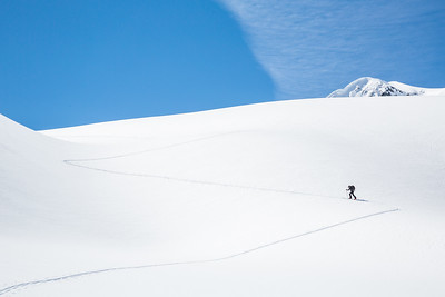 Skinning up the Asulkan Glacier in Glacier National Park, British Columbia. A man hikes on skis to access the Seven Steps to Paradise run in the backcountry of Canada.