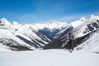 Man skins up the track toward the Asulkan Glacier and the Seven Steps to Paradise backcountry ski run. Behind him is the Trans-Canada Highway and Roger's Pass area