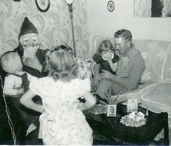 December 24 My Mother sitting on Grandpas lap, far right...and a very very disturbing Santa!