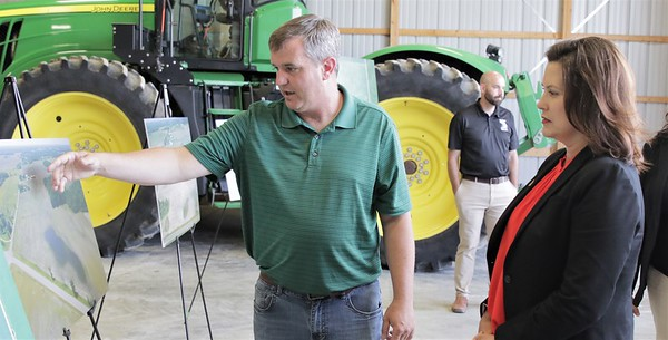 Duane Smuts shows Gov. Whitmer a recent aerial of some of his unplanted farmland.