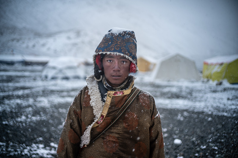 A young yak herder pauses at Base Camp at 17,000' feet to pose for the camera. Often shy or superstitious, thinking that the camera steals their soul, Tibetans are typically reluctant to pause for the camera. A younger generation, however, slowly becomes modernized and is less weary to the ways of old.