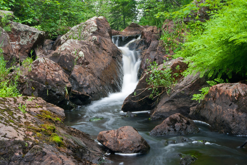 Ely Falls flows through a deep pink-tinged rocky ravine and is located in a remote area not far from the town of National Mine Michigan