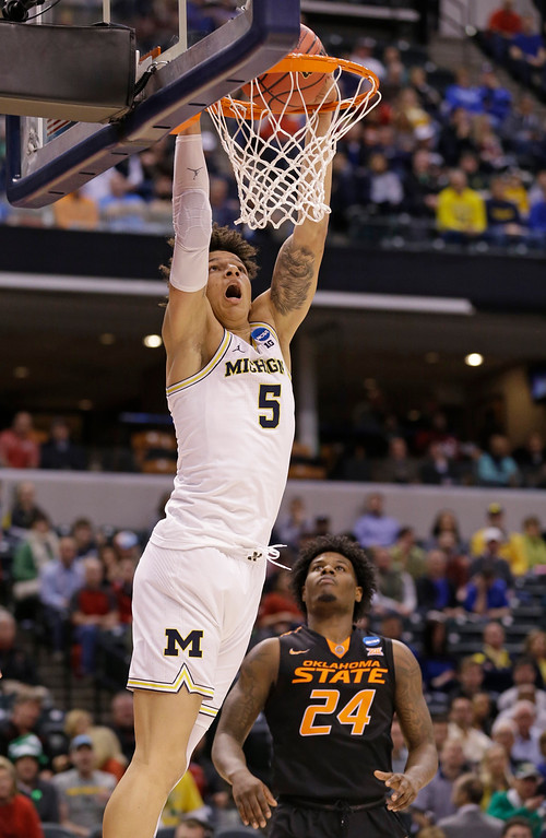 . Michigan forward D.J. Wilson (5) goes up for a dunk over Oklahoma State guard Davon Dillard (24) during a first-round game in the men\'s NCAA college basketball tournament in Indianapolis, Friday, March 17, 2017. (AP Photo/Michael Conroy)