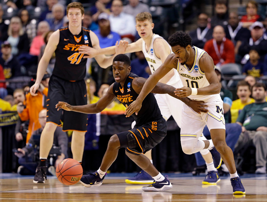 . Michigan guard Derrick Walton Jr. (10) makes a steal from Oklahoma State guard Jawun Evans (1) during a first-round game in the men\'s NCAA college basketball tournament in Indianapolis, Friday, March 17, 2017. (AP Photo/Michael Conroy)