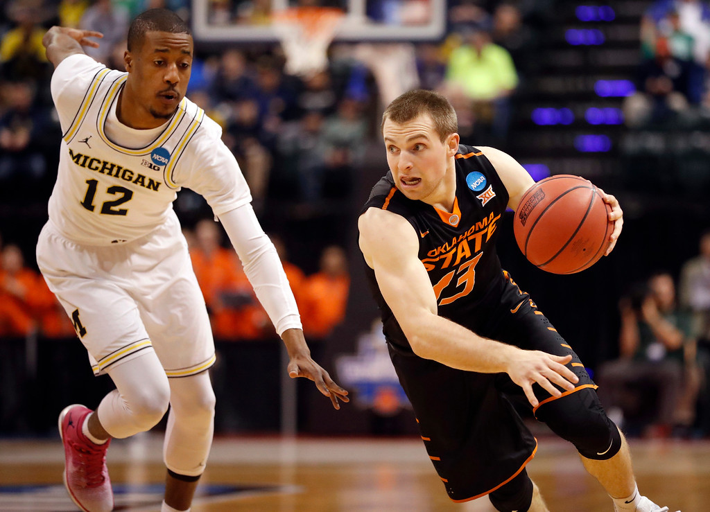 . Oklahoma State\'s Phil Forte III, right, heads to the basket as Michigan\'s Muhammad-Ali Abdur-Rahkman defends during the first half of a first-round game in the men\'s NCAA college basketball tournament Friday, March 17, 2017, in Indianapolis, Mo. (AP Photo/Jeff Roberson)