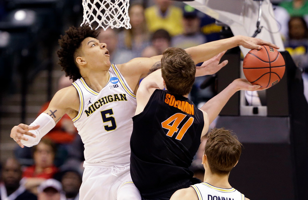 . Michigan forward D.J. Wilson (5) blocks the shot of Oklahoma State forward Mitchell Solomon (41) during a first-round game in the men\'s NCAA college basketball tournament in Indianapolis, Friday, March 17, 2017. (AP Photo/Michael Conroy)