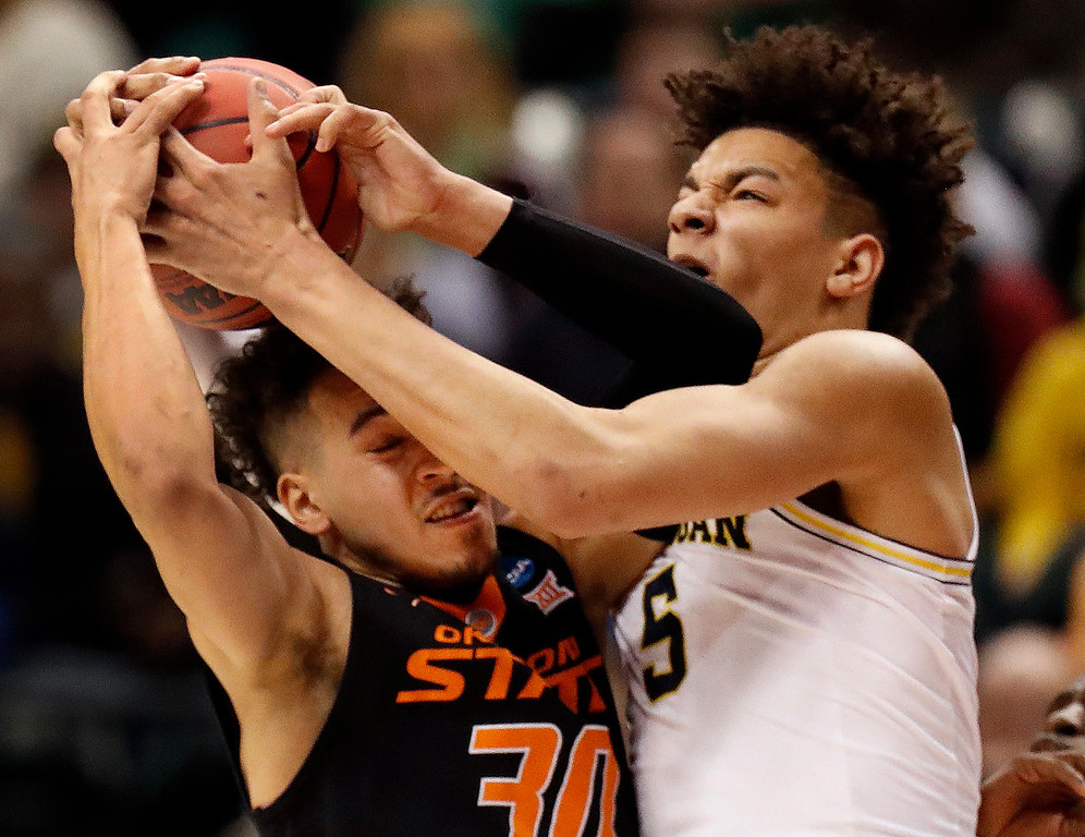 . Oklahoma State\'s Jeffrey Carroll, left, and Michigan\'s D.J. Wilson reach for a rebound during the first half of a first-round game in the men\'s NCAA college basketball tournament Friday, March 17, 2017, in Indianapolis, Mo. (AP Photo/Jeff Roberson)