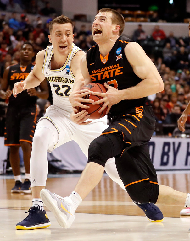 . Oklahoma State\'s Phil Forte III, right, is fouled on his way to the basket by Michigan\'s Duncan Robinson during the first half of a first-round game in the men\'s NCAA college basketball tournament Friday, March 17, 2017, in Indianapolis, Mo. (AP Photo/Jeff Roberson)