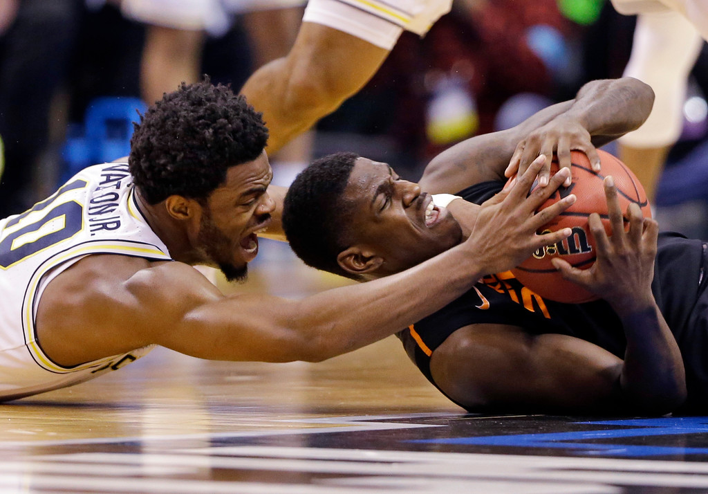 . Michigan guard Derrick Walton Jr. (10), left, and Oklahoma State guard Jawun Evans (1) scramble for a loose ball during a first-round game in the men\'s NCAA college basketball tournament in Indianapolis, Friday, March 17, 2017. (AP Photo/Michael Conroy)