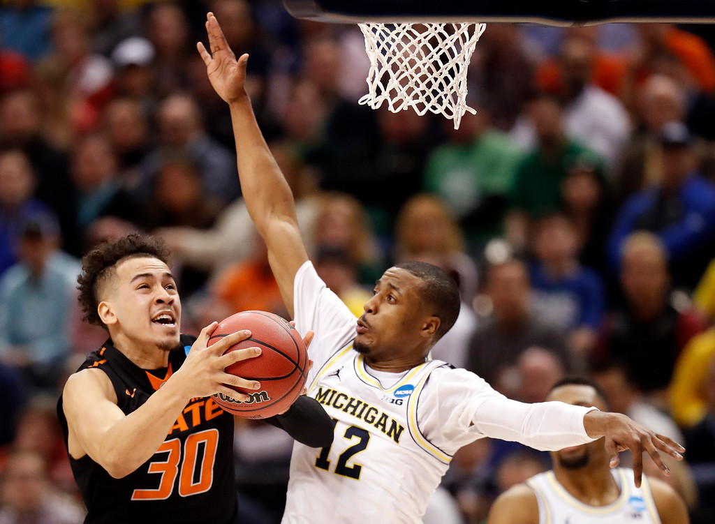 . Oklahoma State\'s Jeffrey Carroll (30) heads to the basket as Michigan\'s Muhammad-Ali Abdur-Rahkman defends during the second half of a first-round game in the men\'s NCAA college basketball tournament Friday, March 17, 2017, in Indianapolis, Mo. Michigan won 92-91. (AP Photo/Jeff Roberson)