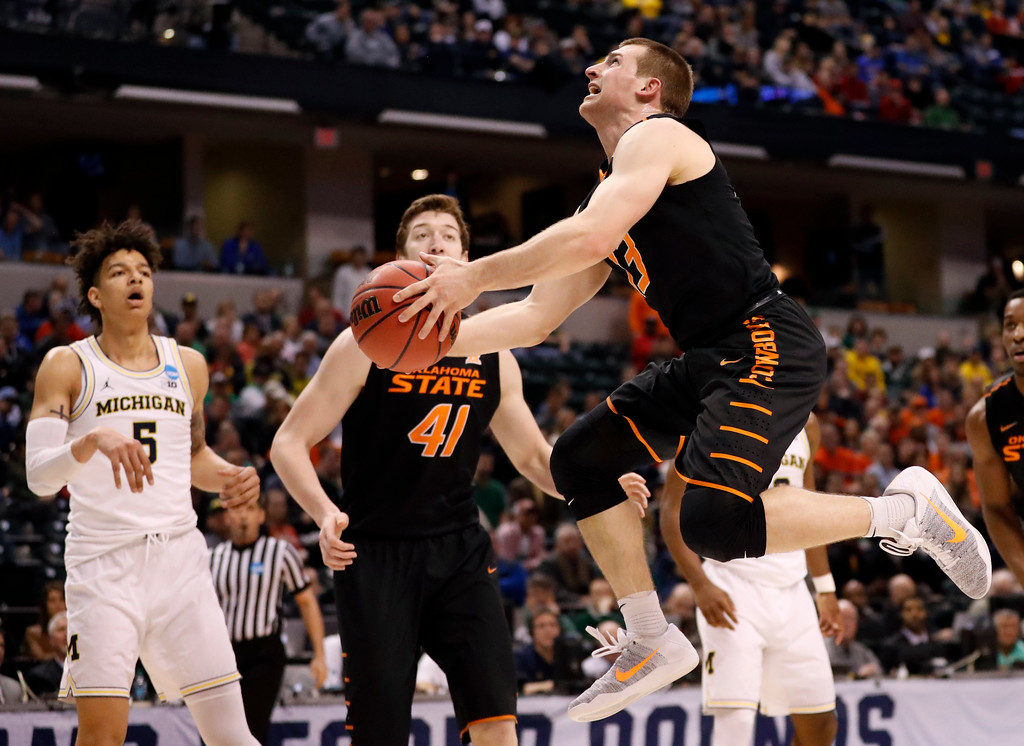 . Oklahoma State\'s Phil Forte III, right, heads to the basket as teammate Mitchell Solomon (41) and Michigan\'s D.J. Wilson, left, watch during the first half of a first-round game in the men\'s NCAA college basketball tournament Friday, March 17, 2017, in Indianapolis, Mo. (AP Photo/Jeff Roberson)