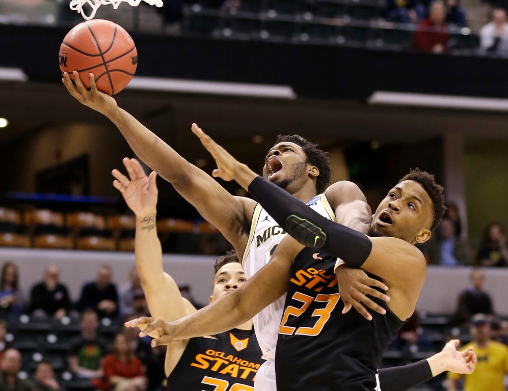 . Michigan guard Derrick Walton Jr. (10) is fouled as he shoots by Oklahoma State forward Leyton Hammonds (23) during a first-round game in the men\'s NCAA college basketball tournament in Indianapolis, Friday, March 17, 2017. (AP Photo/Michael Conroy)