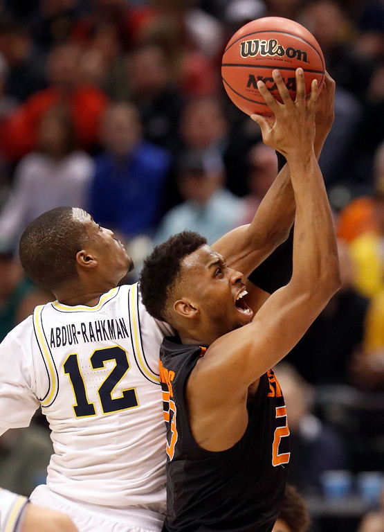 . Oklahoma State\'s Leyton Hammonds, right, is unable to make it to the basket as Michigan\'s Muhammad-Ali Abdur-Rahkman (12) defends during the second half of a first-round game in the men\'s NCAA college basketball tournament Friday, March 17, 2017, in Indianapolis, Mo. Michigan won 92-91. (AP Photo/Jeff Roberson)