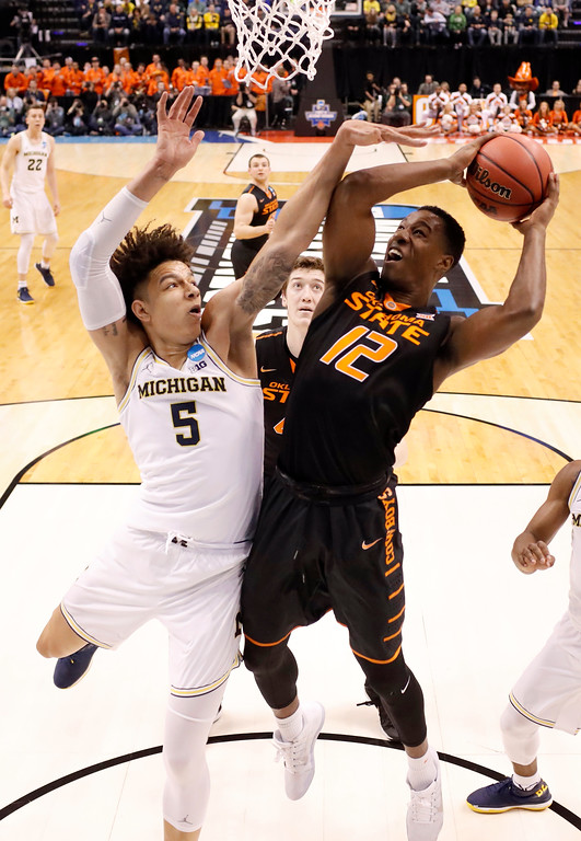 . Oklahoma State\'s Cameron McGriff (12) heads to the basket as Michigan\'s D.J. Wilson (5) defends during the first half of a first-round game in the men\'s NCAA college basketball tournament Friday, March 17, 2017, in Indianapolis, Mo. (AP Photo/Jeff Roberson)