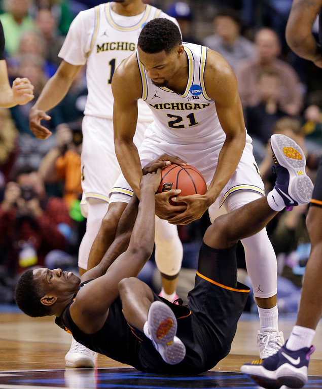 . Oklahoma State guard Jawun Evans (1) and Michigan guard Zak Irvin (21) fight for a loose ball during a first-round game in the men\'s NCAA college basketball tournament in Indianapolis, Friday, March 17, 2017. (AP Photo/Michael Conroy)