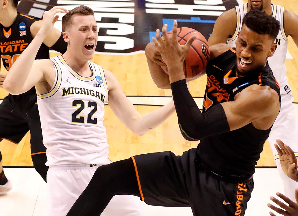 . Oklahoma State\'s Leyton Hammonds, right, pulls down a rebound as Michigan\'s Duncan Robinson watches during the second half of a first-round game in the men\'s NCAA college basketball tournament Friday, March 17, 2017, in Indianapolis, Mo. Michigan won 92-91. (AP Photo/Jeff Roberson)